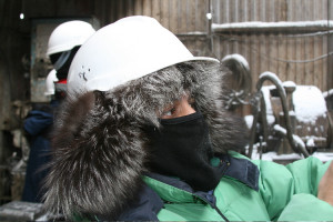 While in Siberia in minus 25 degrees Farenheit on an oil installation, Ken wears a fur-lined helmut while filming the workers drilling for natural gas.