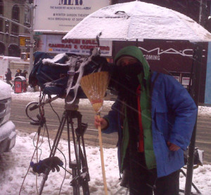 A broom can be very helpful while shooting in a blizzard. Here in Times Square in 2011 while the snow piles up.