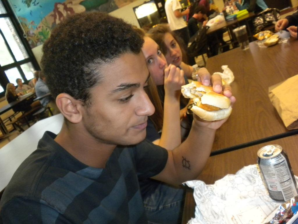 Deep+in+thought+while+finishing+his+lunch%2C+student+Khalil+Williams+demonstrates+the+versatility+of+a+chicken+patty.++
