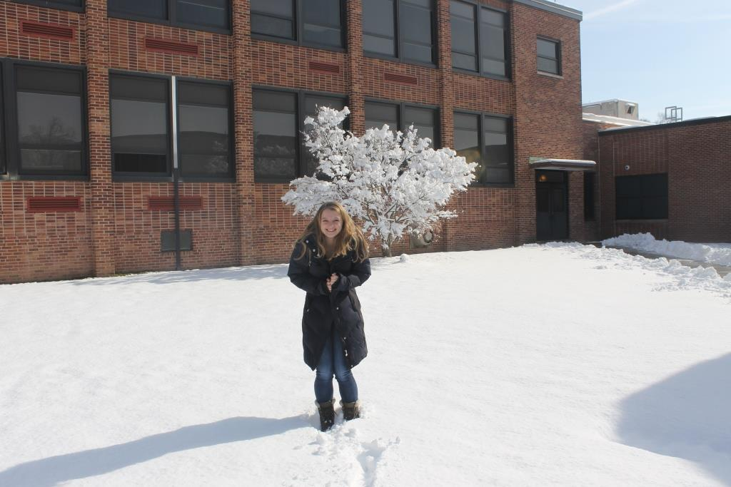 Erica Melz, quite cold in the polar vortext, attempts to stay warm in the high school courtyard.