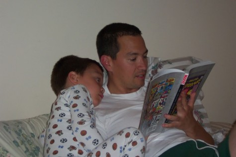 Christopher listens intently while his father reads a comic book to him.