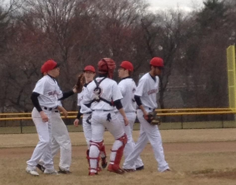 The+baseball+team+gathers+on+the+mound+between+innings%2C+prior+to+the+brunt+of+the+oncoming+storm.