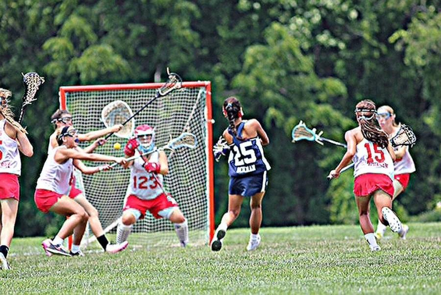 As she breaks through a swarm of defense, Alex Beilman scores a goal against her opponents.