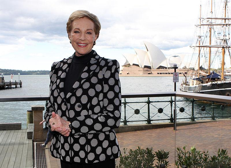 Smiling in a queenly fashion, Andrews poses in front of the Sydney Opera House.