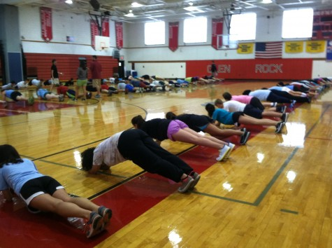 Physical Education students do planks for warm-ups.