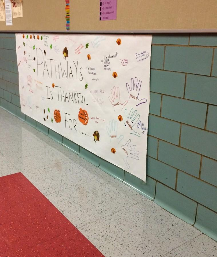 Young kids at the annual Pathways Thanksgiving event decorate the sign hanging in the senior hallway to show what they're thankful for.