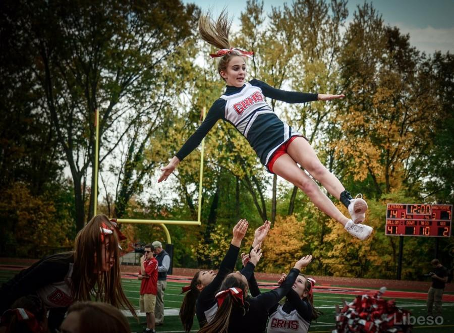 Cheerleader Sophia Arnao, cheerleading as a flyer, performs a stunt with the help from her bases.  Recently, Arnao has transitioned to a base spot on the team.