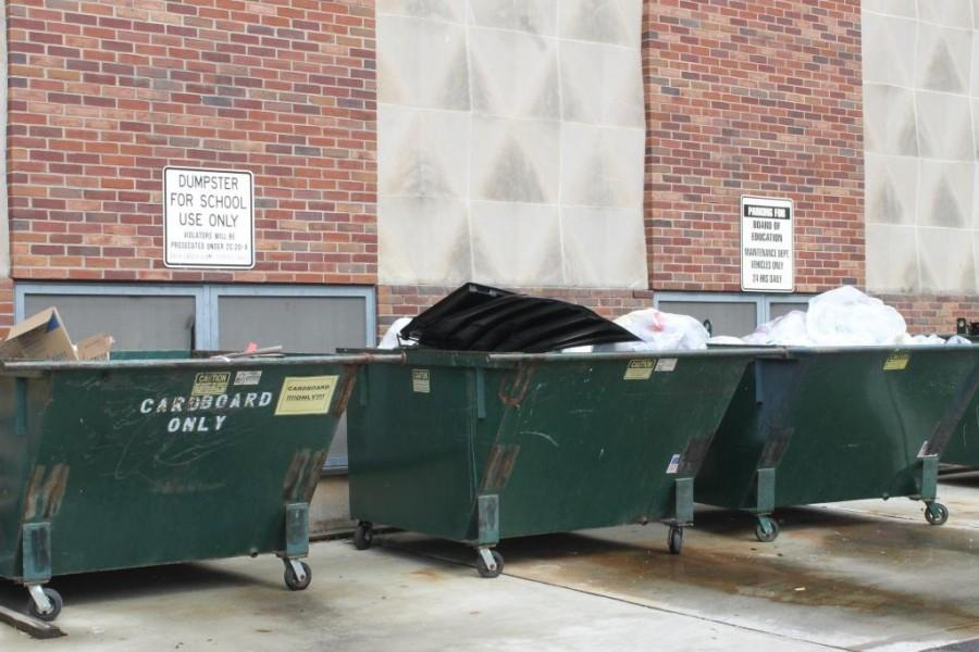 The garbage dumpsters outside of the Sports Lobby serve as the pickup location for the school's waste.