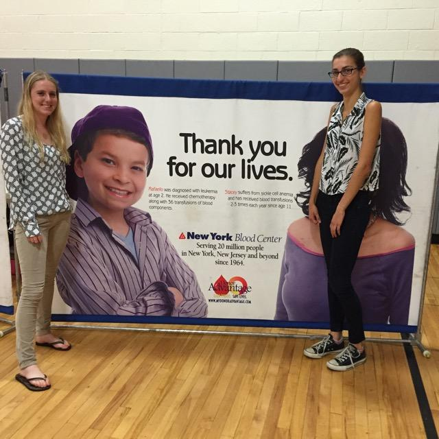 Celia Hans and Mikaela Rosen, the two coordinators of the blood drive, stand by a New York Blood Drive sign.