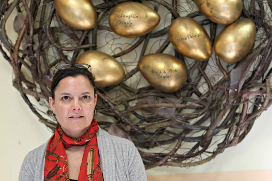 Executive Director Jennifer Brady stands in front of Oasis' nest inscribed with generous benefactors.