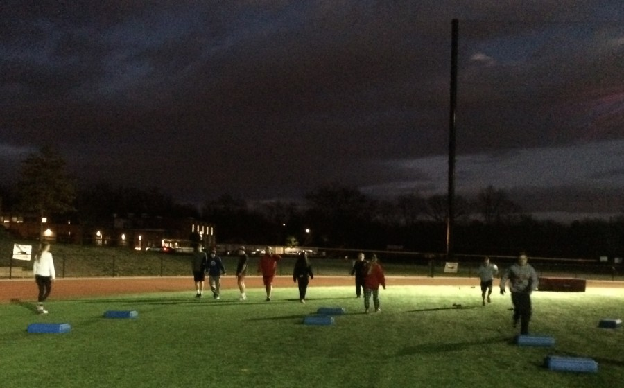 Winter track athletes train outside under the lights thanks to the unseasonably warm weather.