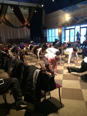 Students learn how to safely fall on stage.