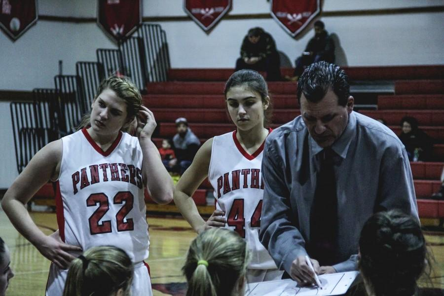 Kelly Lohr (17) and Cate McLoughlin (18) listen to Coach Steve Grenzs play to win the game.
