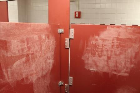 Scratches from the janitors from getting rid of the graffiti can be seen on the stall walls