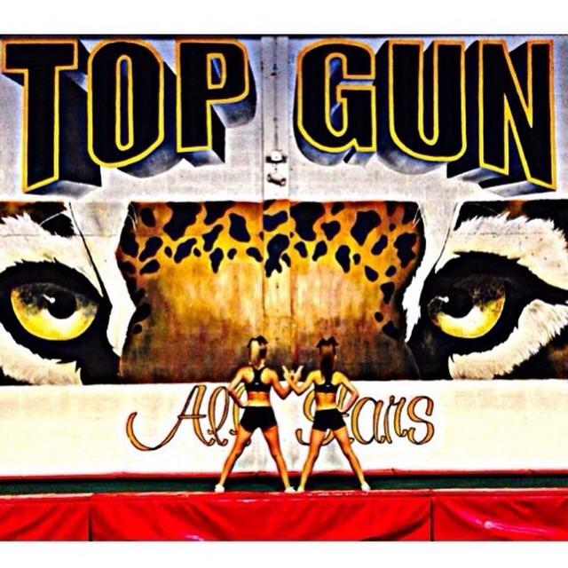 Christina and Natalie posing in front of the TopGun Jags Banner