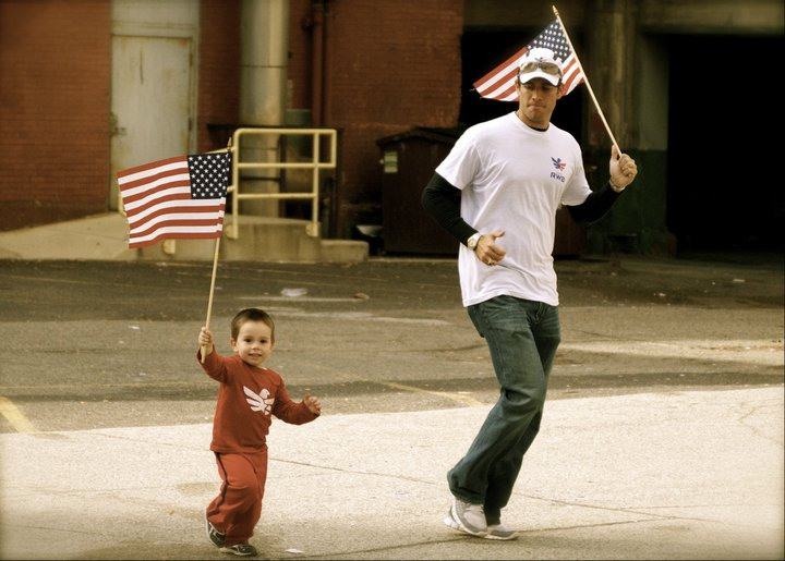 Jonathan Algor and his oldest son, Jack, run with the flag at the Detroit Marathon. Jack was born when Algor was still serving in Iraq and they didn't meet until he was three months old (Photo Credit: Jonathan Algor)