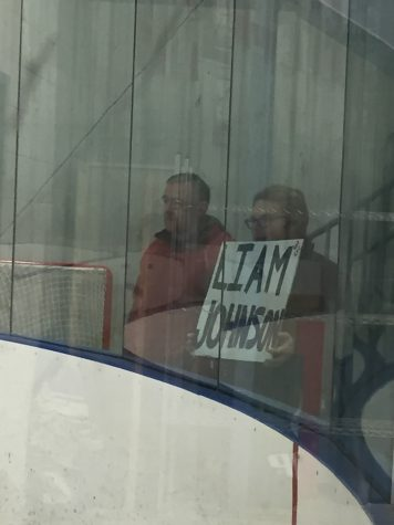 "Indian Hills student holding a ""Liam Johnson"" sign against the glass for Johnson and all to see."