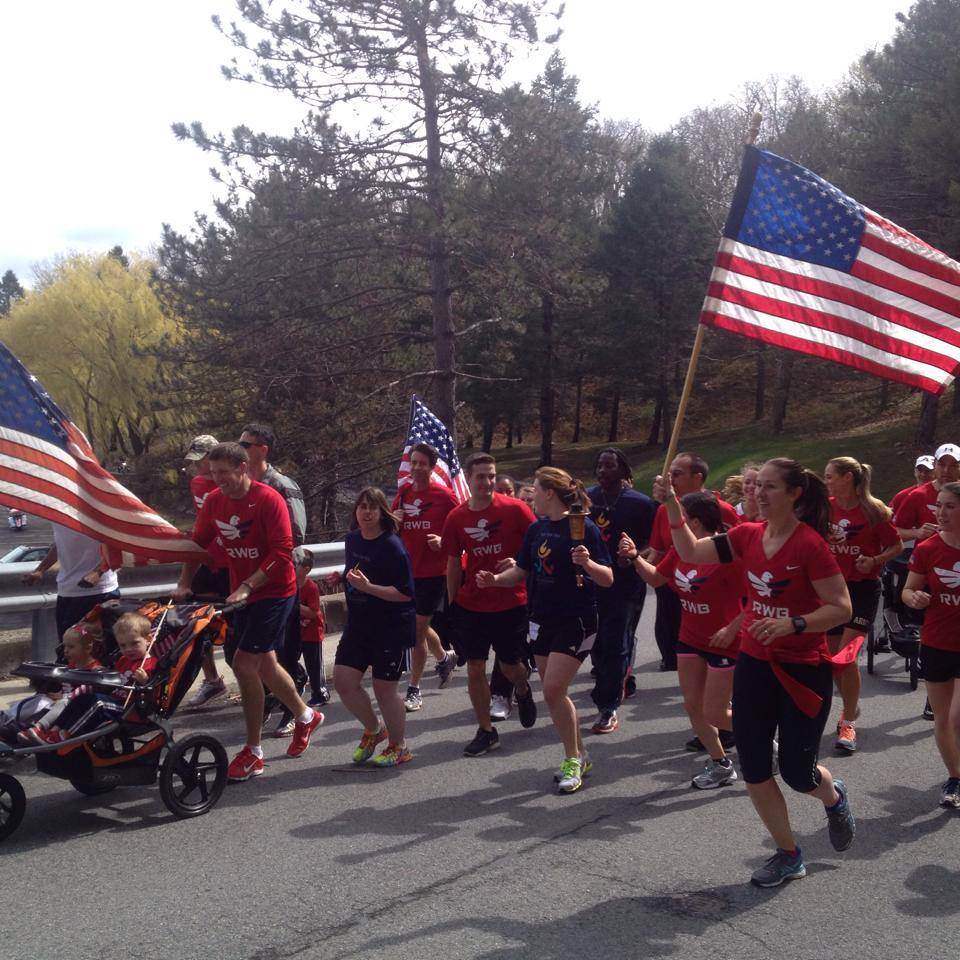 "Team Red, White & Blue runs with the flag at the Special Olympics Marathon. The organization stands out at running events by carrying an American flag and wearing ""We are the Eagle"" tee-shirts (Photo Credit: Jonathan Algor)"