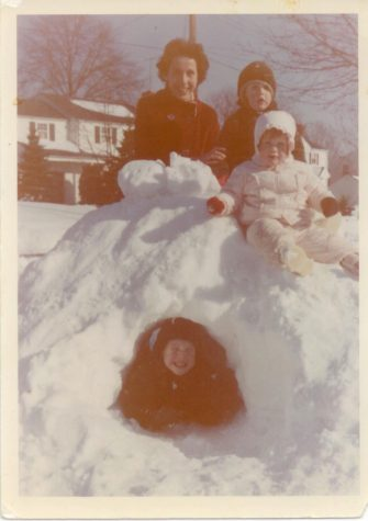 Dot Zier and three of her four children, Ron, Julie, and Ed build an igloo in the front yard of their home on Greenway Road.