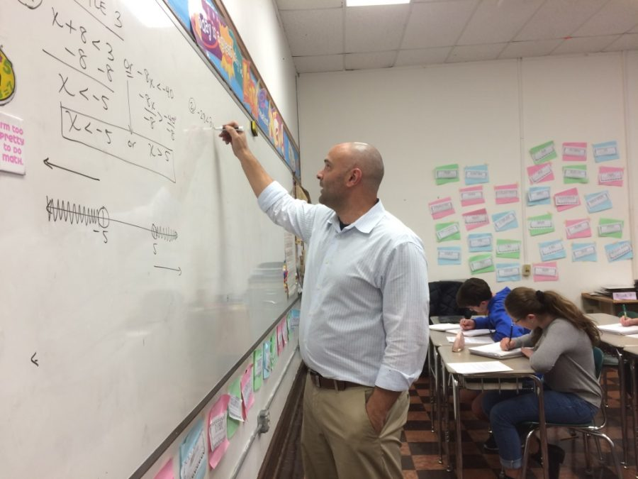 Mr. Carlo Santaniello teaches to his middle school class, while they attentively take notes and further their understanding of slope.