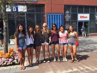 Players of the girls' varsity tennis team pose in front of an entrance to the U.S. Open.
