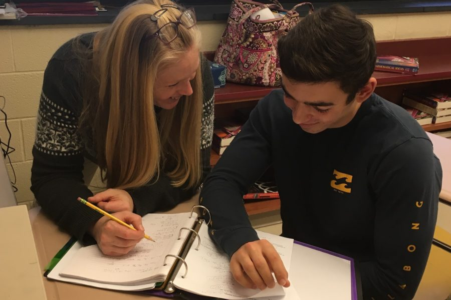 Mrs. Stacie Gallo reviews an assignment with junior Dominic Patania.