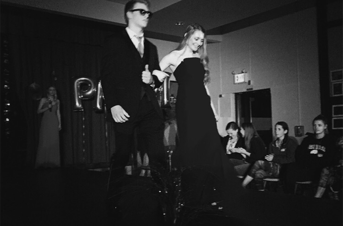 Senior Matt Schlett accompanies junior Katie Kelly down the runway.