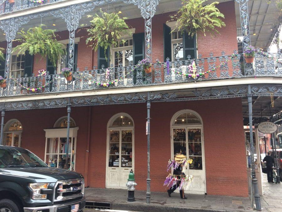 A man walks through the French Quarter streets bearing flowers. Above, Mardi Gras decorations are still hanging up.