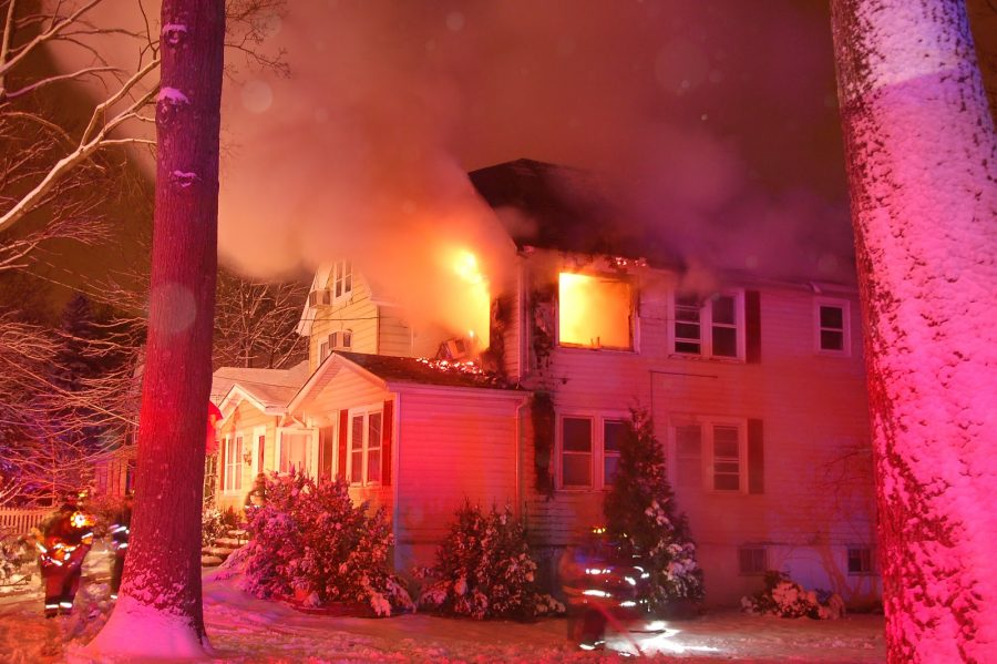 The Greene's home glows a rufescent shade of red from flames and police lights in the early hours of the morning. The fire sprouted at approximately 1 a.m. and was bridled by roughly 3:30 a.m.
