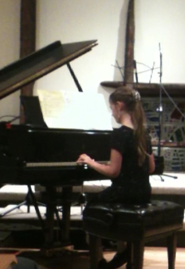 10-year-old Claire Beezley plays the piano at her teacher's annual concert. She was very nervous before the recital and tried her best to distract herself from playing to calm down.