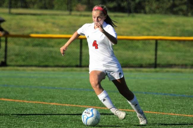 Sweeper Mary Geen drives the ball up towards the field. This game was located at the Glen Rock High School soccer field.