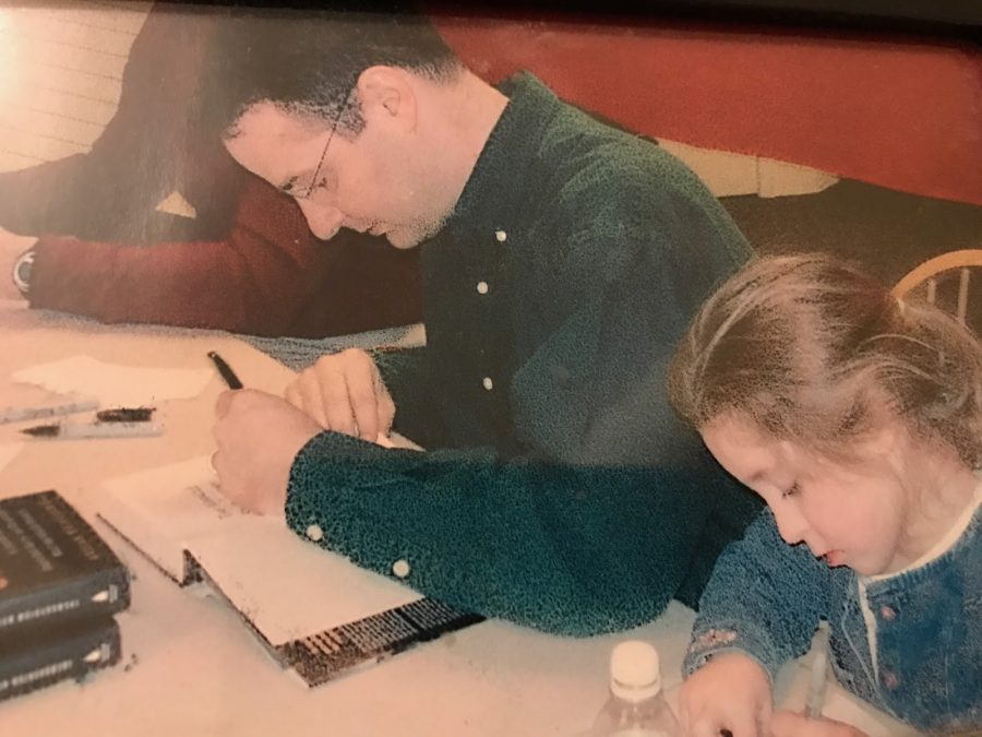 Leaving a mark on the opening pages of The Miracle of St. Anthony, author Wojnarowski signs his name. Alongside him sat his daughter, Annie Wojnarowski, uniquely signing her name as well.