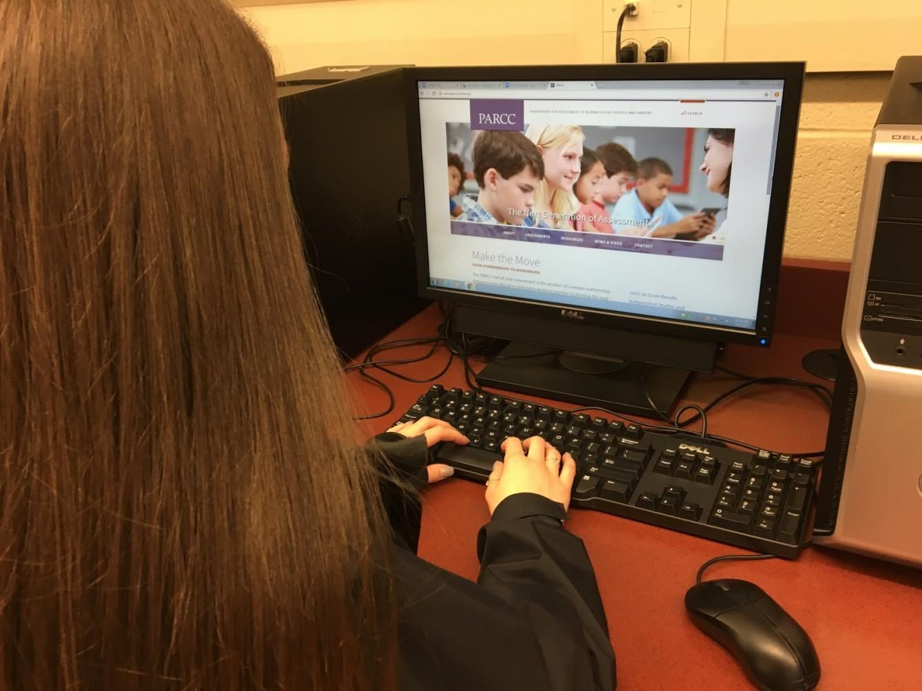 A student types away at her computer while researching the PARCC.