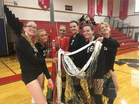 The girls hold up a net after their win against Lodi.