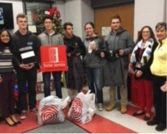 Students pose in front of gift drive presents.