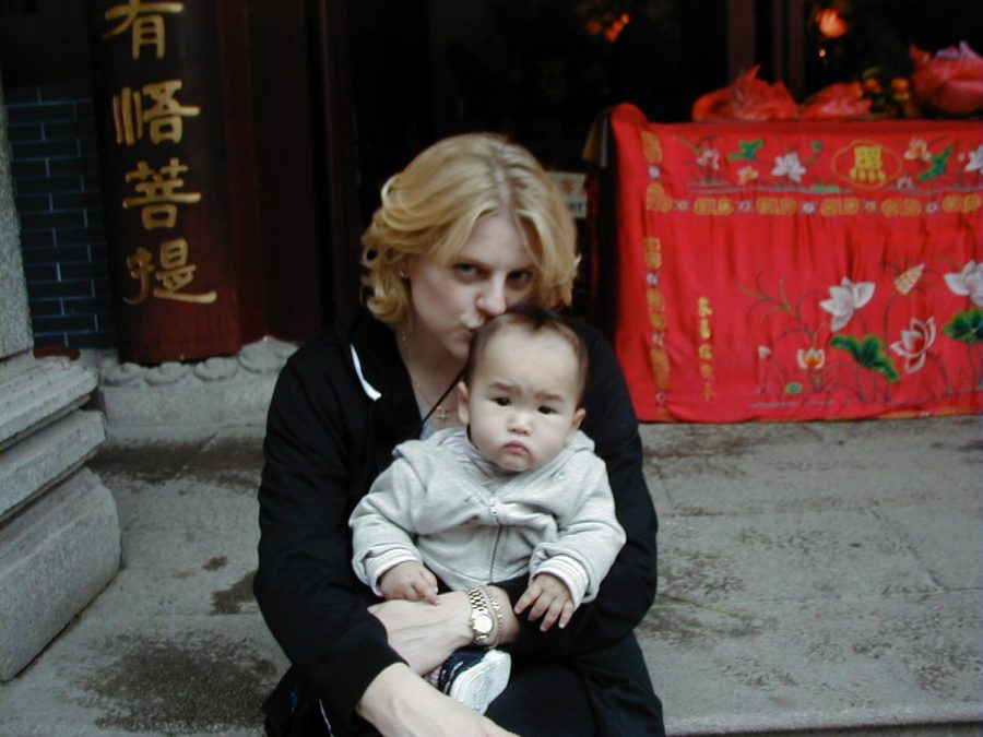 New mom Robin Huisking calms her daughter for a photo on a Chinese sidewalk in 2003.