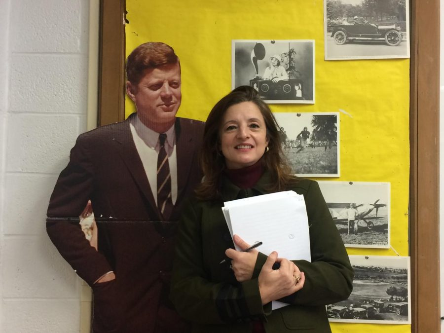 "Kathleen Walter poses with her cardboard cutout of President John F. Kennedy. She felt that this would be appropriate because of his famous quote regarding Berlin, ""Ich bin ein Berliner. I too am a Berliner."""