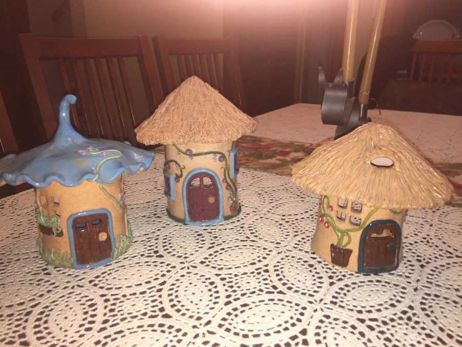 Three clay lanterns shaped like small  houses. Barbra keeps these on display in her home, and illuminates them with small candles.