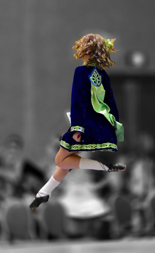 Alissa is leaping high in the air in an Irish dance competition in 2017.