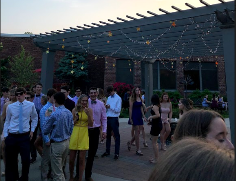 Students flourish under the courtyard pergola that is flooded with lights to match the dance's theme.