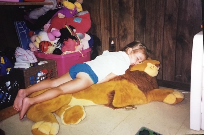 Zacks younger sister Gabby laying on the simba stuffed animal the hospital bought him.