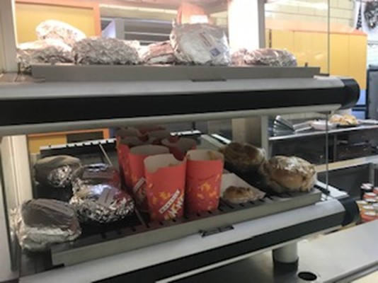 This is a picture of popular lunch selections in the cafeteria right now. This includes a selection of wrapped burgers, sandwiches, wraps, chicken nuggets and french fries.
