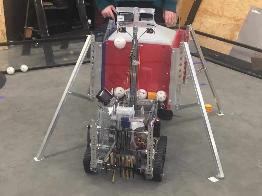 The team's robot retrieves Wiffle balls on a FTC game board. In order to do so, it follows a script of code written by the team. The programming is being fed to the robot through a phone strapped to the machine.