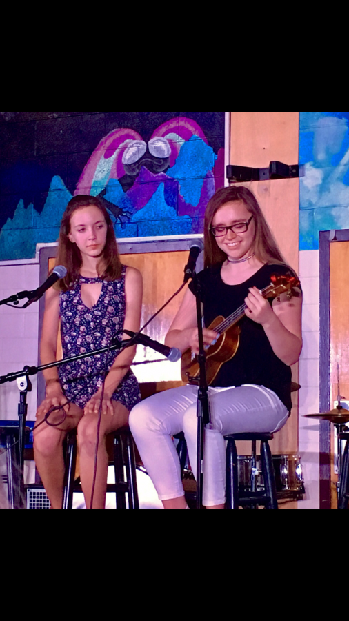 Dylaney Sabino (right) and Caitlin O'Brien (left) sing at the spring Coffeehouse their freshmen year.