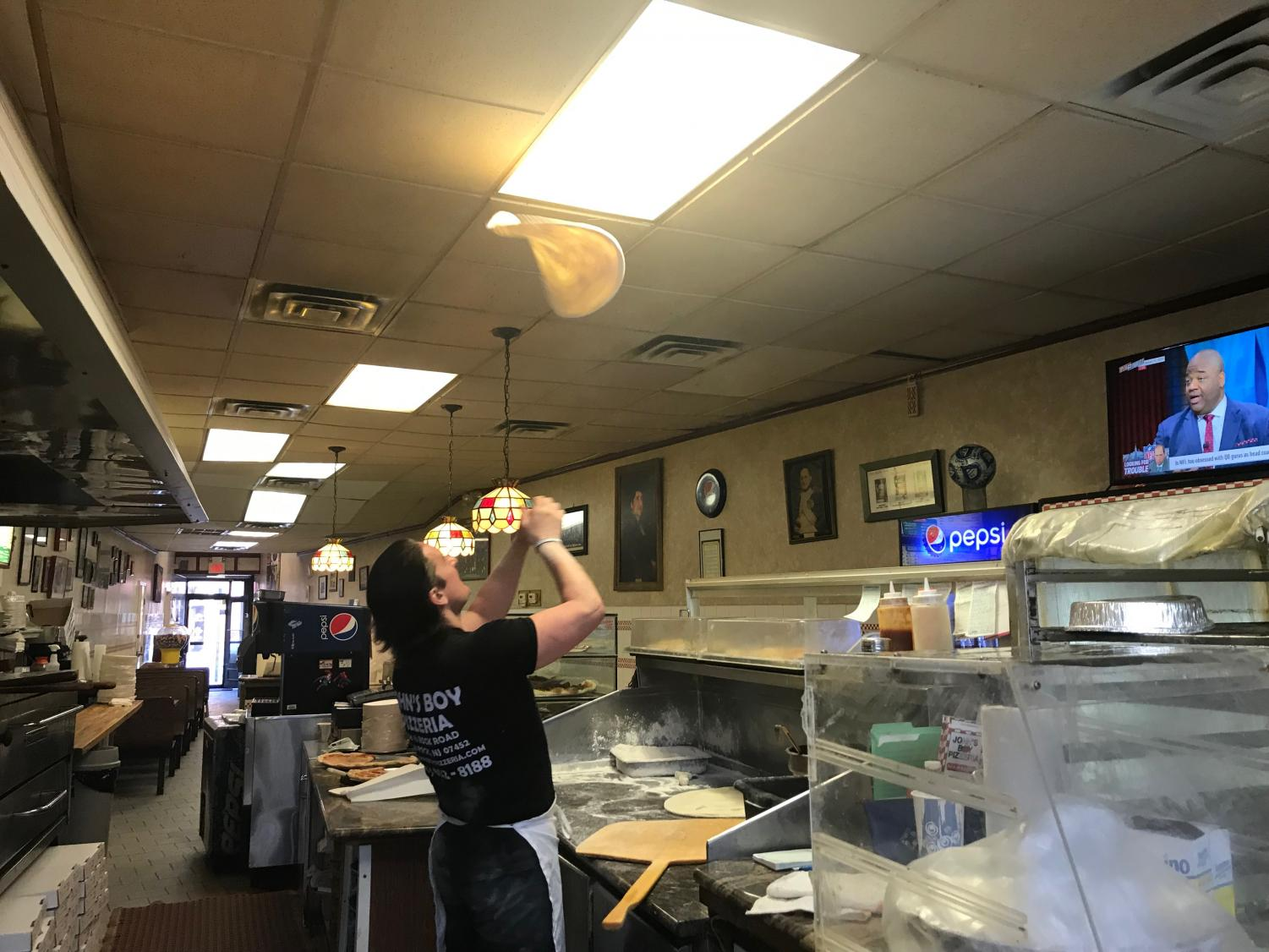 Umberto throwing the pizza dough in the air as he prepares to make a pie for a customer.