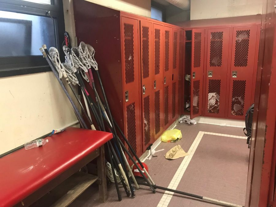 Defenders lacrosse sticks are shoved into a back corner of the room, unable to fit in players lockers.