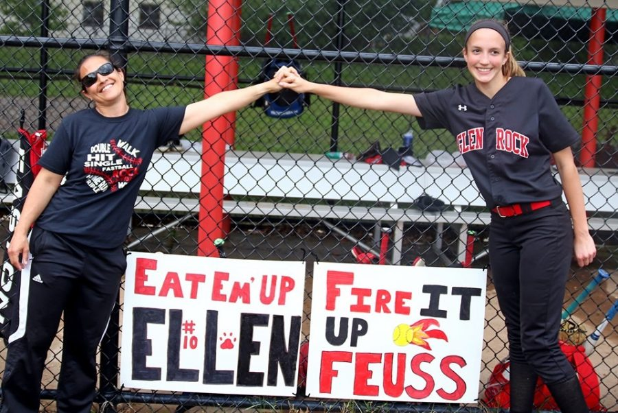 """Here is Ellen Feuss (right) and Coach Dowell (left) showing their """"coach to captain"""" relationship while standing over man made signs supporting Ellen and making it obvious that she will be missed next year by Dowell and the rest of the team."""