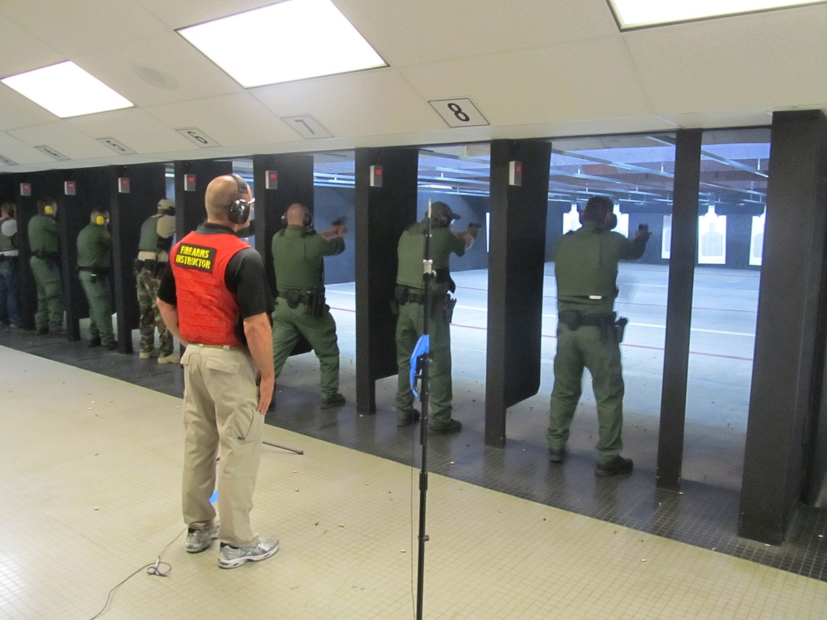 Federal law enforcement officers during firearms training exercises at indoor firing range