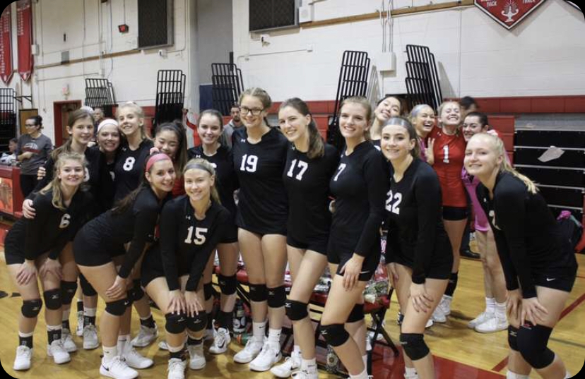 Members+of+the+varsity+volleyball+team+pose+for+a+celebratory+picture+after+a+victory+on+Senior+Day+on+Oct.+24%2C+2019.+%0A