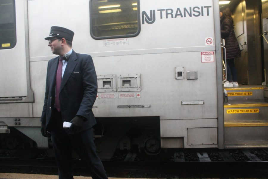One of the conductors on the train waits just outside one of the open train car doors to ensure that all of the waiting commuters have boarded the train and the train is clear to leave the Glen Rock-Main Line station.